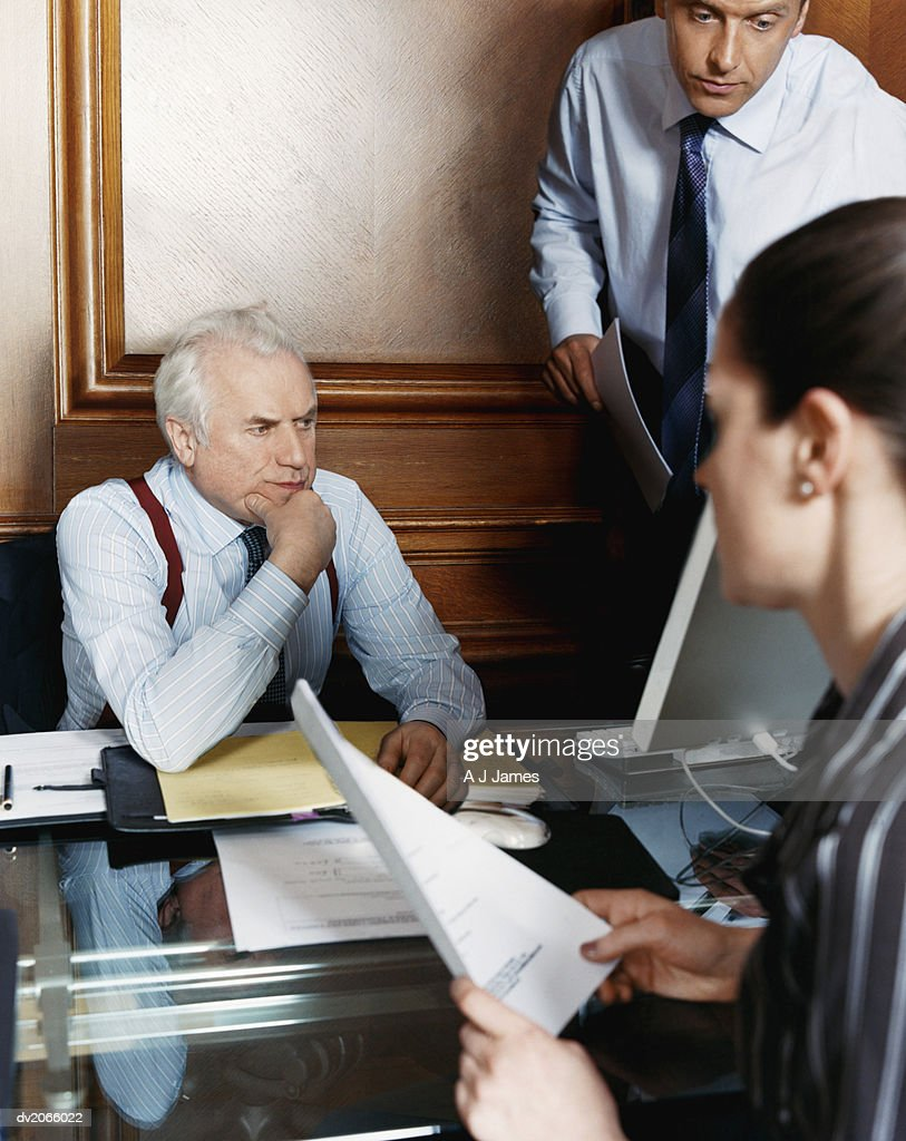 Business Executives Working Around a Senior CEO's Desk : Stock Photo