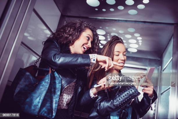 Business Females Online Shopping On Smartphone In Elevator After Work