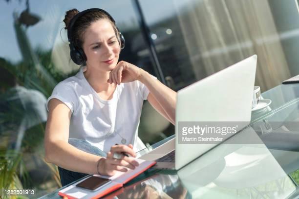 business frau im homeoffice mit laptop beim online meeting auf terrasse - frau fotografías e imágenes de stock