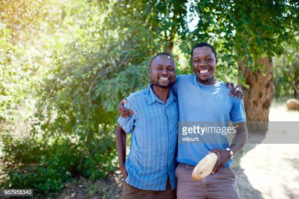 business friends standing together under a tree - zimbabwe stock pictures, royalty-free photos & images