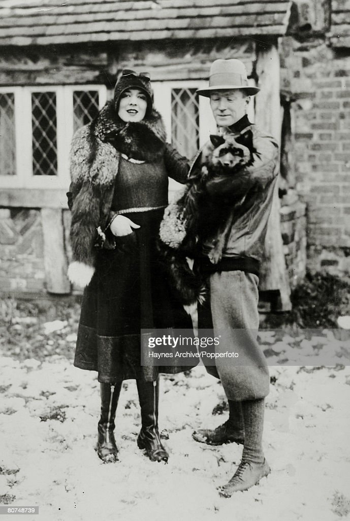 Business Fur. pic: 1929. An attractive young woman wearing a fur poses in outdoor style clothes with a man holding a silver fox at a fur farm in Kent, England. : Photo d'actualité