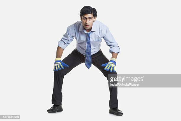Business goalkeeper ready to save the goal over white background