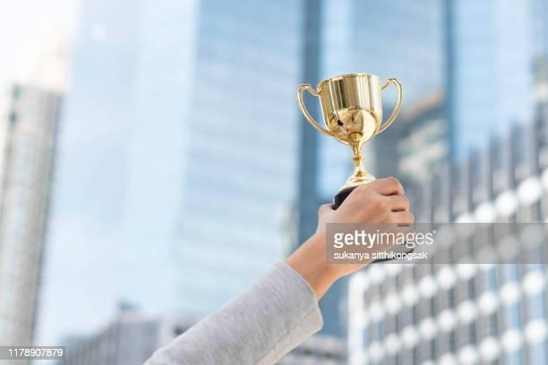 business goals,business concept.close up hand of businesswoman holding gold trophy. - premio fotografías e imágenes de stock