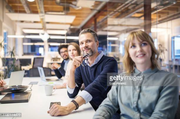business group attending video conference call in board room - bijwonen stockfoto's en -beelden