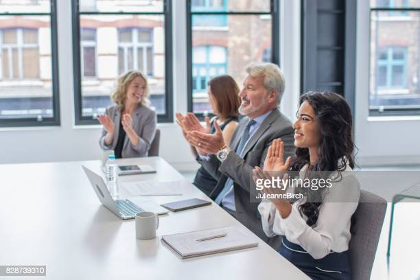 business group clapping after office meeting - shareholder's meeting stock photos and pictures