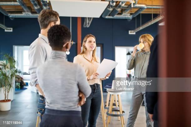 business group having a standing meeting in office - envolvimento dos funcionários - fotografias e filmes do acervo