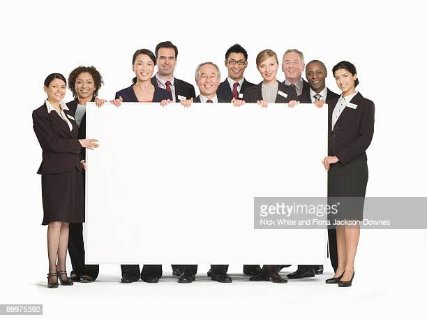 A business group holding a white board