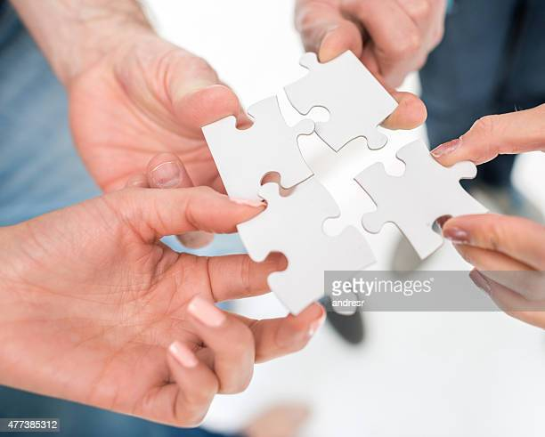 Business group putting pieces of a puzzle together