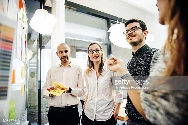 business group standing close to whiteboard - quatre personnes photos et images de collection