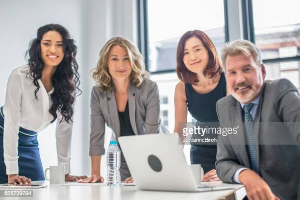 business group working together in london office - shareholder's meeting stock photos and pictures