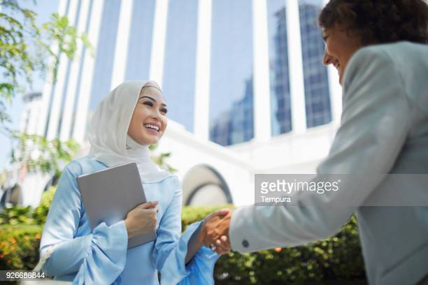 business hand shake. - malay stock photos and pictures