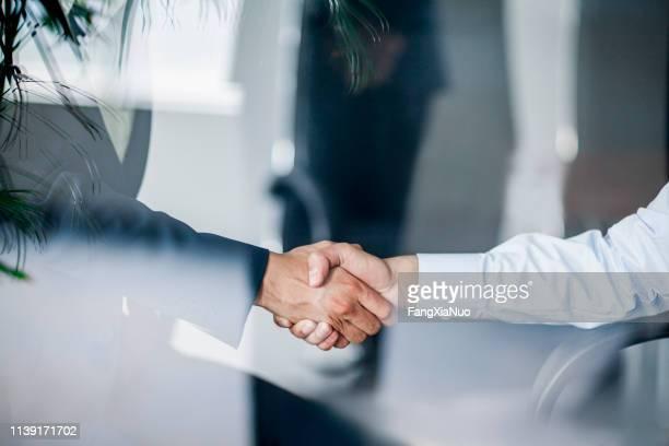 business handshake in glas reflectie in office - top vergadering stockfoto's en -beelden