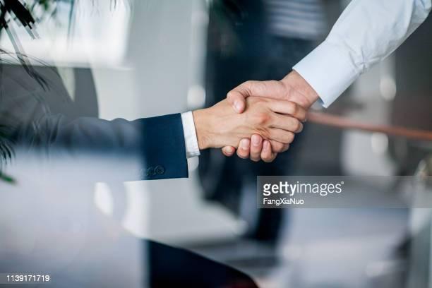 business-handschlag in glasreflexion im büro - human body part stock-fotos und bilder