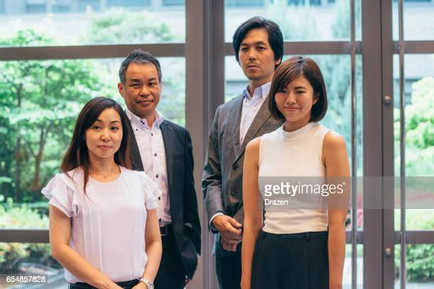 Business in Japan - Group of Japanese male and female business people in corporate building