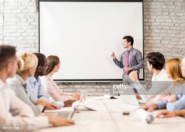 Business instructor giving presentation to large group of people