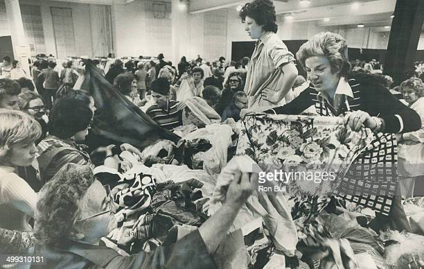 Business is brisk for Martha Greenbaum and Bertha Savlove as they stand on top of the pile of clothing while bargaining with some of the 60000...
