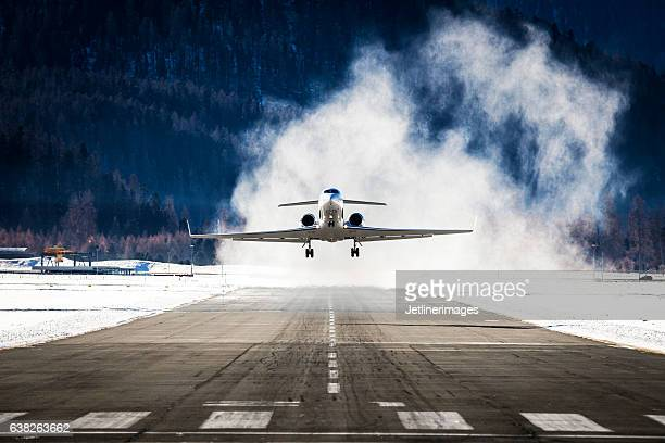 business jet departing a snowy airfield - airfield stock pictures, royalty-free photos & images