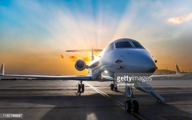 business jet on ramp with sun in background - private aeroplane stock pictures, royalty-free photos & images