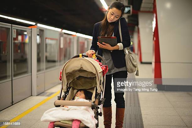 Business lady talking on mobile pushing stroller