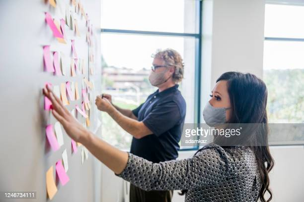 business leaders brainstorming with notes - brainstorming stock pictures, royalty-free photos & images