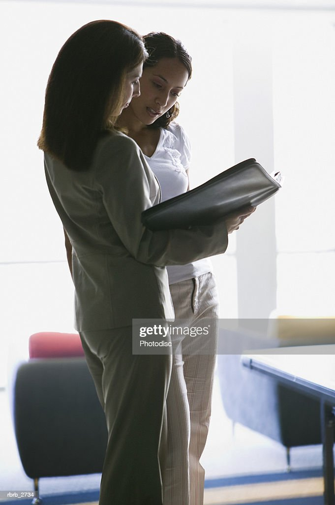 business lifestyle shot of a young adult woman as she goes over some paperwork with a coworker : Foto de stock