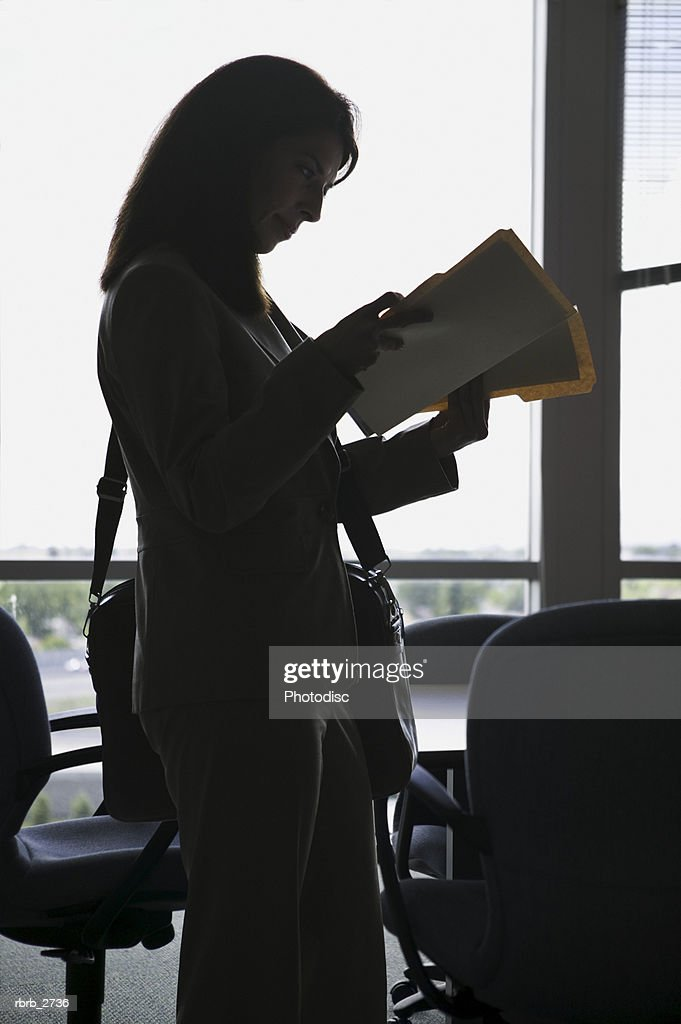 business lifestyle shot of a young adult woman as she goes through a file in her office : Foto de stock