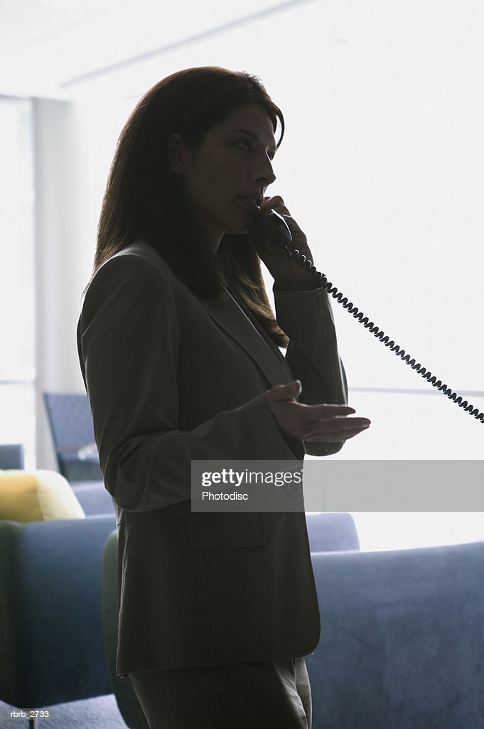 business lifestyle shot of a young adult woman as she makes a call from a telephone : Foto de stock
