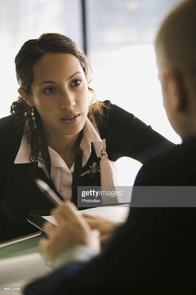 business lifestyle shot of a young adult woman as she sits in a meeting with her supervisor : Foto de stock