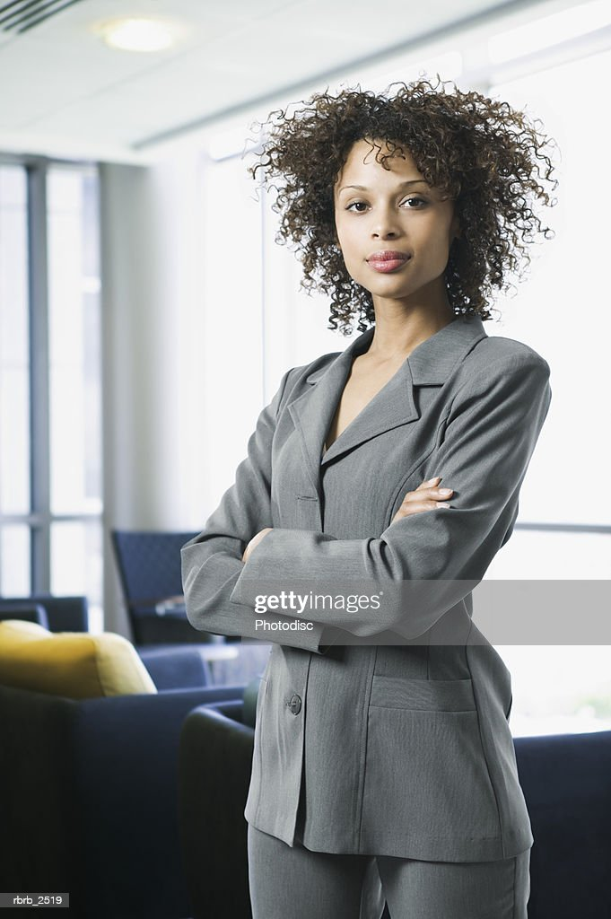 business lifestyle shot of a young adult woman in a grey suit as she folds her arms and smiles : Foto de stock