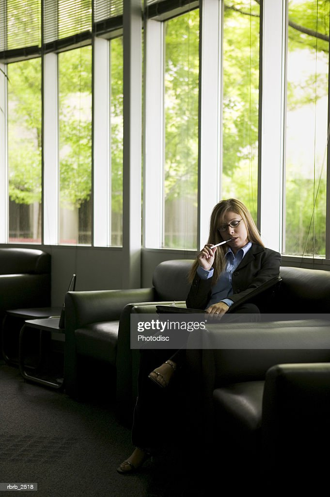 business lifestyle shot of an adult woman as she reviews her notes in an office lobby : Foto de stock