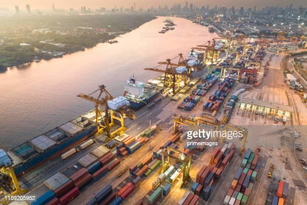 日の出時の造船所での作業クレーン橋を備えたコンテナ貨物船・貨物のビジネスロジスティクスと輸送、物流輸入輸出・輸送業界の背景 - indonesia logistics ストックフォトと画像