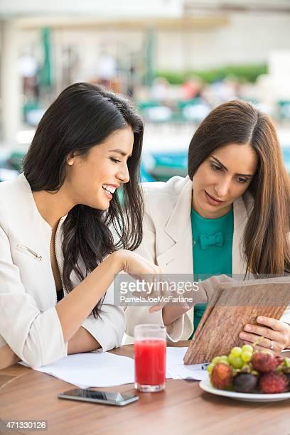 Business Lunch, zwei Middle Eastern Geschäftsfrauen Sie einen Tablet PC
