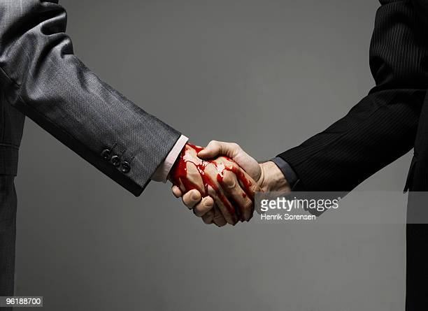 Business males shaking hands with blood