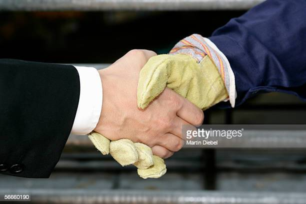 A business man and a construction worker shaking hands