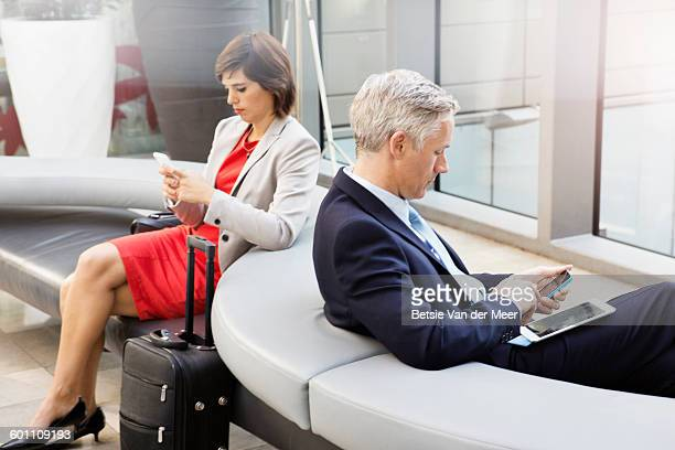 Business man and woman in lobby at airport.