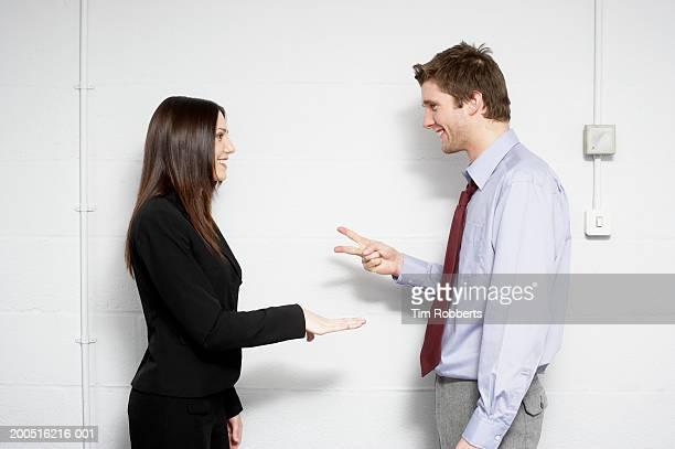 business man and woman playing paper, scissors, stones, side view