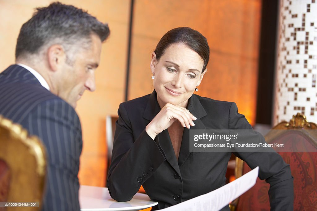 Business man and woman reading documents in hotel lobby : Stock Photo