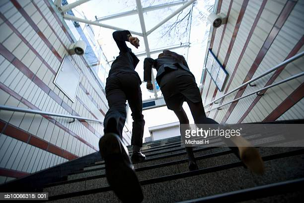 Business man and woman running up stairs, low angle view