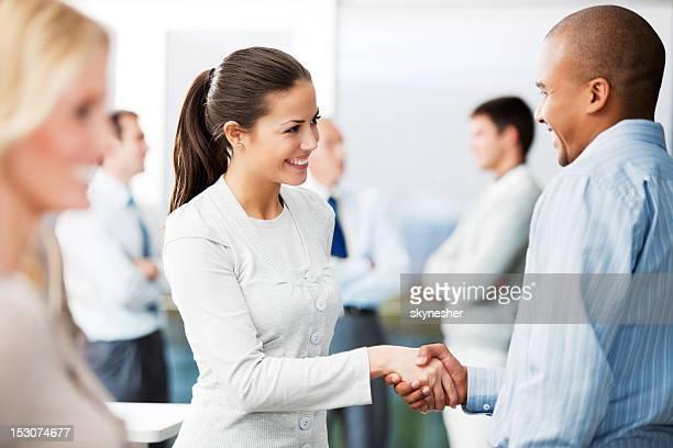 Hombre y mujer de negocios estrechándose las manos.