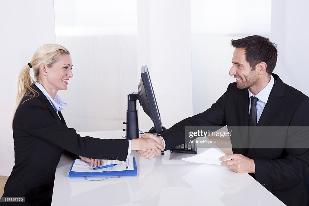 Business man and woman shaking hands : Stock Photo
