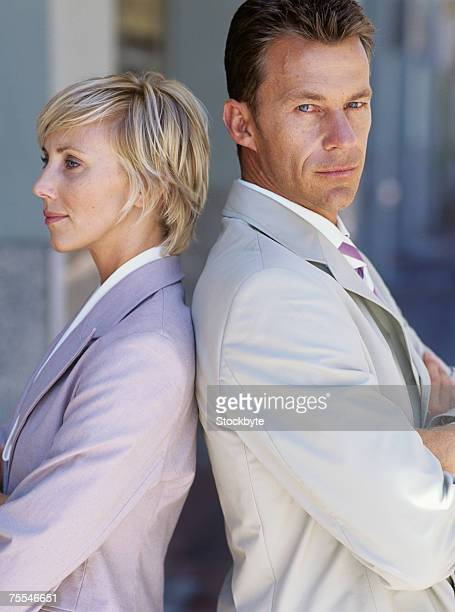 Business man and woman standing back to back with crossed arms,man looking at camera
