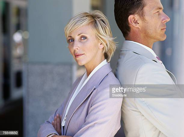 Business man and woman standing back to back with crossed arms,woman looking at camera
