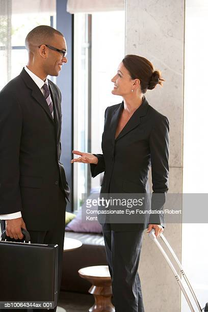 Business man and woman talking in hotel lobby