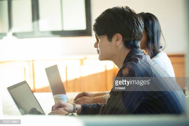 Business man and woman using laptop at meeting room