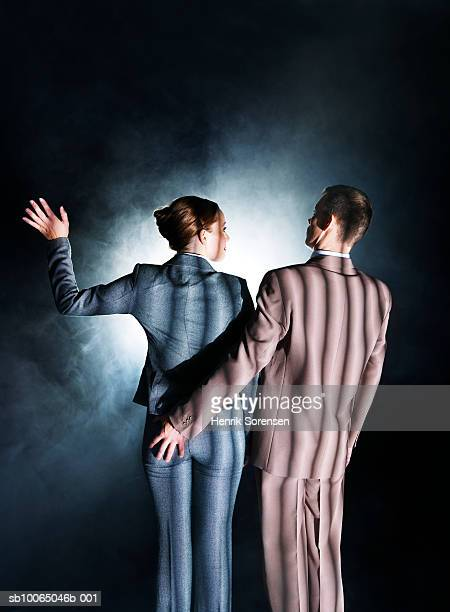 Business man and woman wearing striped suits facing spotlight, rear view