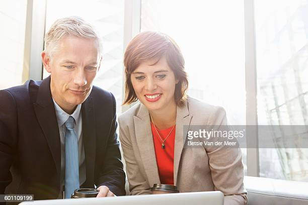 Business man and woman working on laptop.