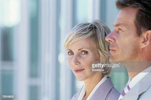 Business man and woman,woman looking at camera,head and shoulders