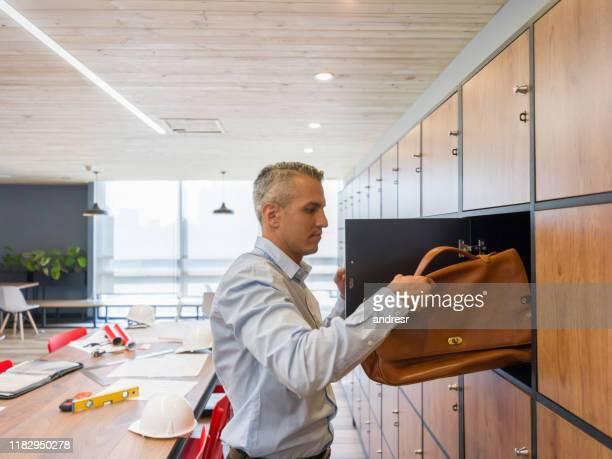 ロッカーにブリーフケースを入れるコワーキングスペースのビジネスマン - ロッカー ストックフォトと画像