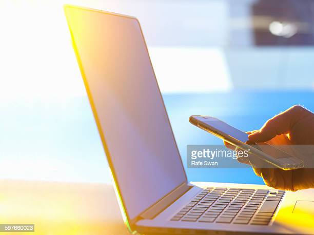 Business man at laptop computer with smartphone in office with sunlight coming through window