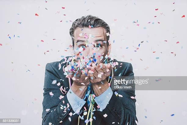 business man blowing confetti. - celebration stock pictures, royalty-free photos & images